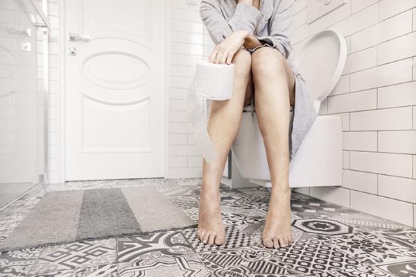 Frau sitzt auf Toilette mit Toilettenpapierrolle in der Hand