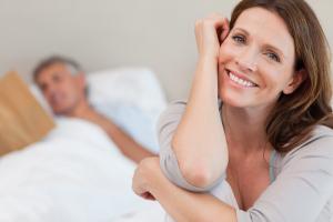 Lächelnde Frau, Mann im Bett im Hintergrund