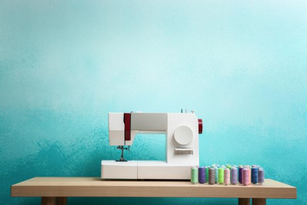 Nähmaschine vor türkisfarbenen Hintergrund
