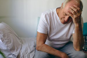 Gestresster älterer Mann auf dem Bett sitzend