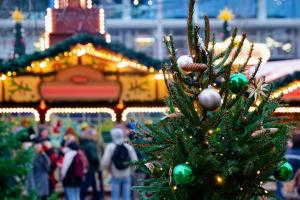 Weihnachtsmarkt mit Tannenzweigen im Vordergrund