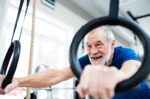 Mann trainiert an Ringen im Fitnessstudio