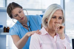 Hustende Frau wird von einer Ärztin untersucht
