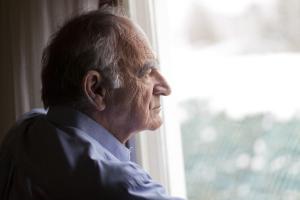 Mann schaut nachdenklich aus dem Fenster