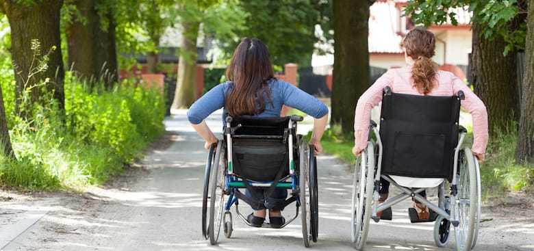 image décorative : deux femmes en fauteuil roulant qui avancent côte à côte dans un parc