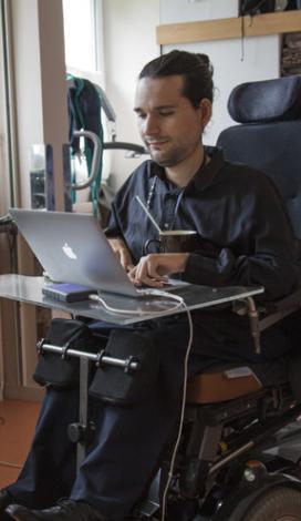 image décorative : une jeune homme en fauteuil roulant électrique avec un ordinateur portable