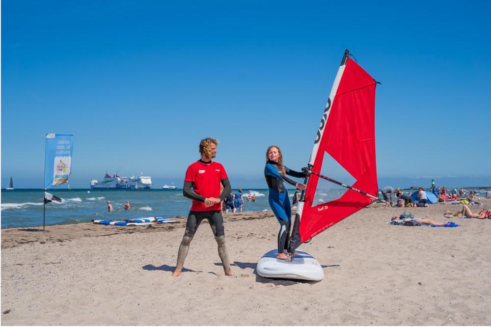 Kind lernt Windsurfen an der Ostsee