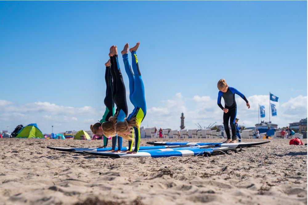 Handstand auf dem Surfbrett am Strand