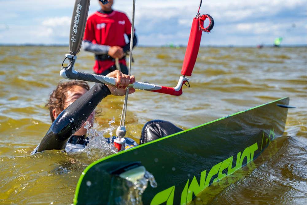 Schülerin beim Wasserstart beim kiten lernen