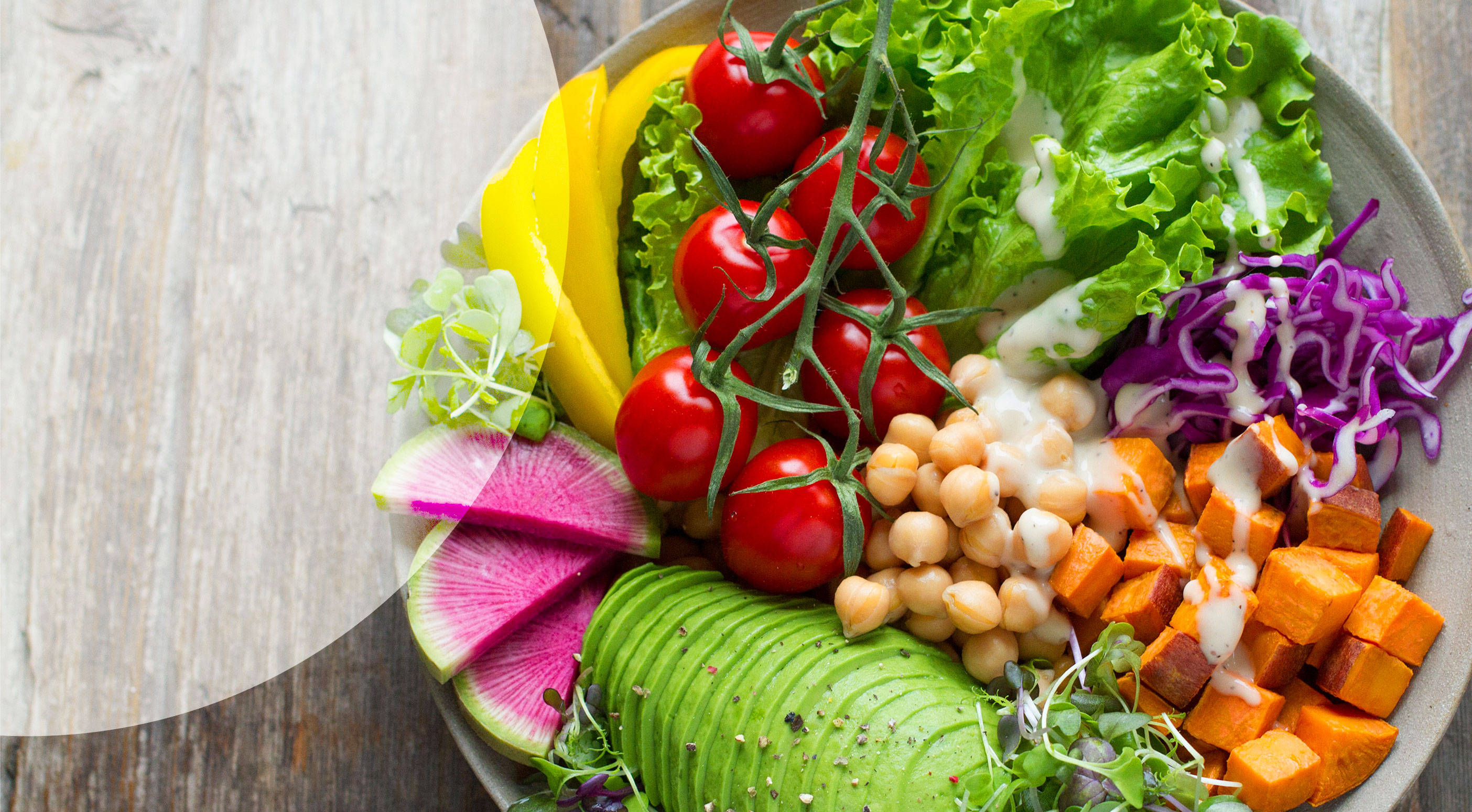 A bowl full of colorful fruits, vegetables, leafy greens, legumes