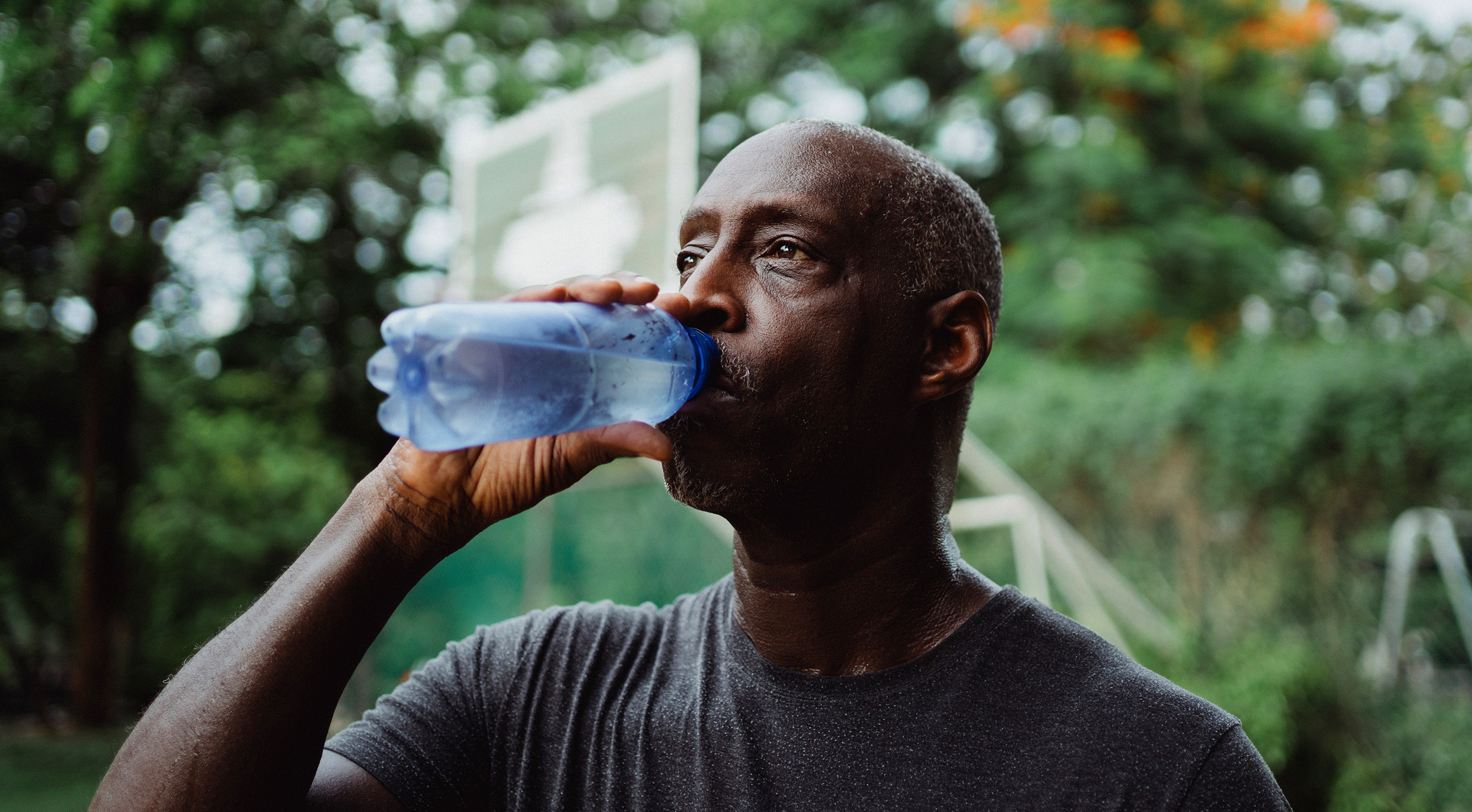 Middle aged man drinking water from a bottle after workout