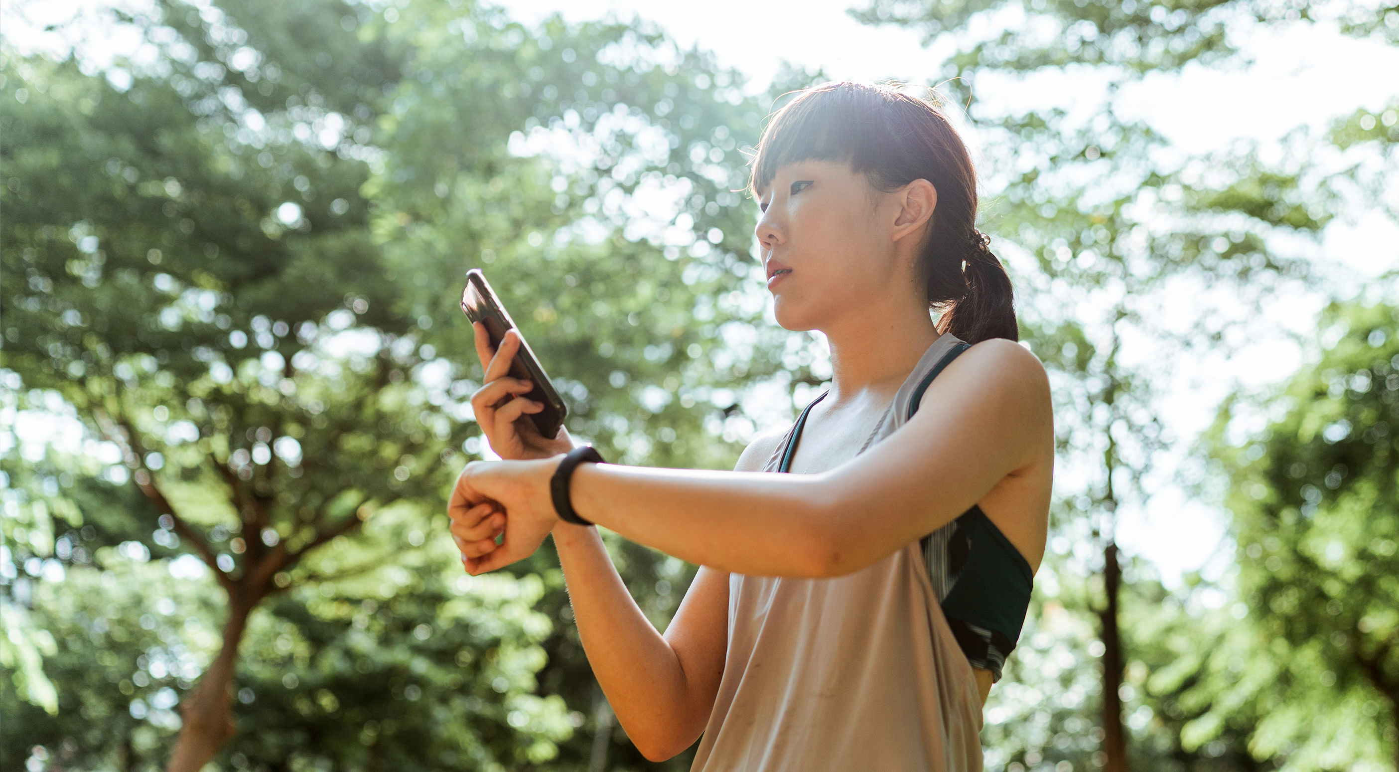 Young woman looking at her phone after a jog in the forest