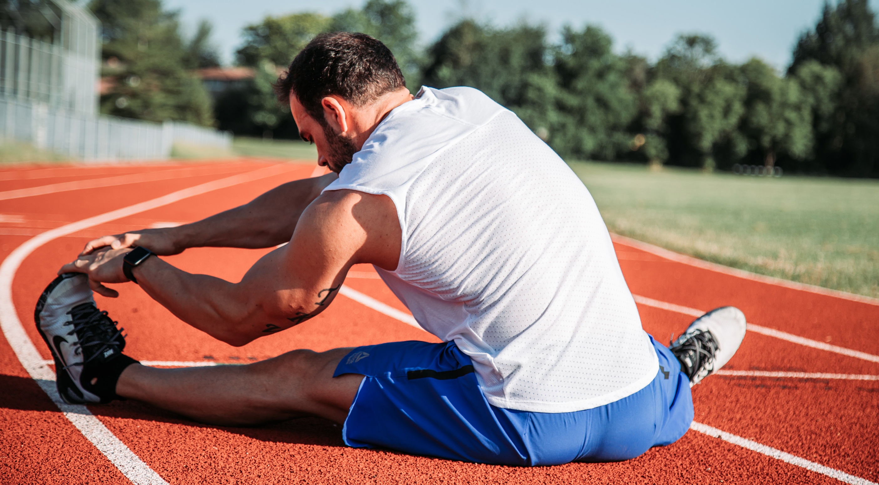 Young man stretching in the running field