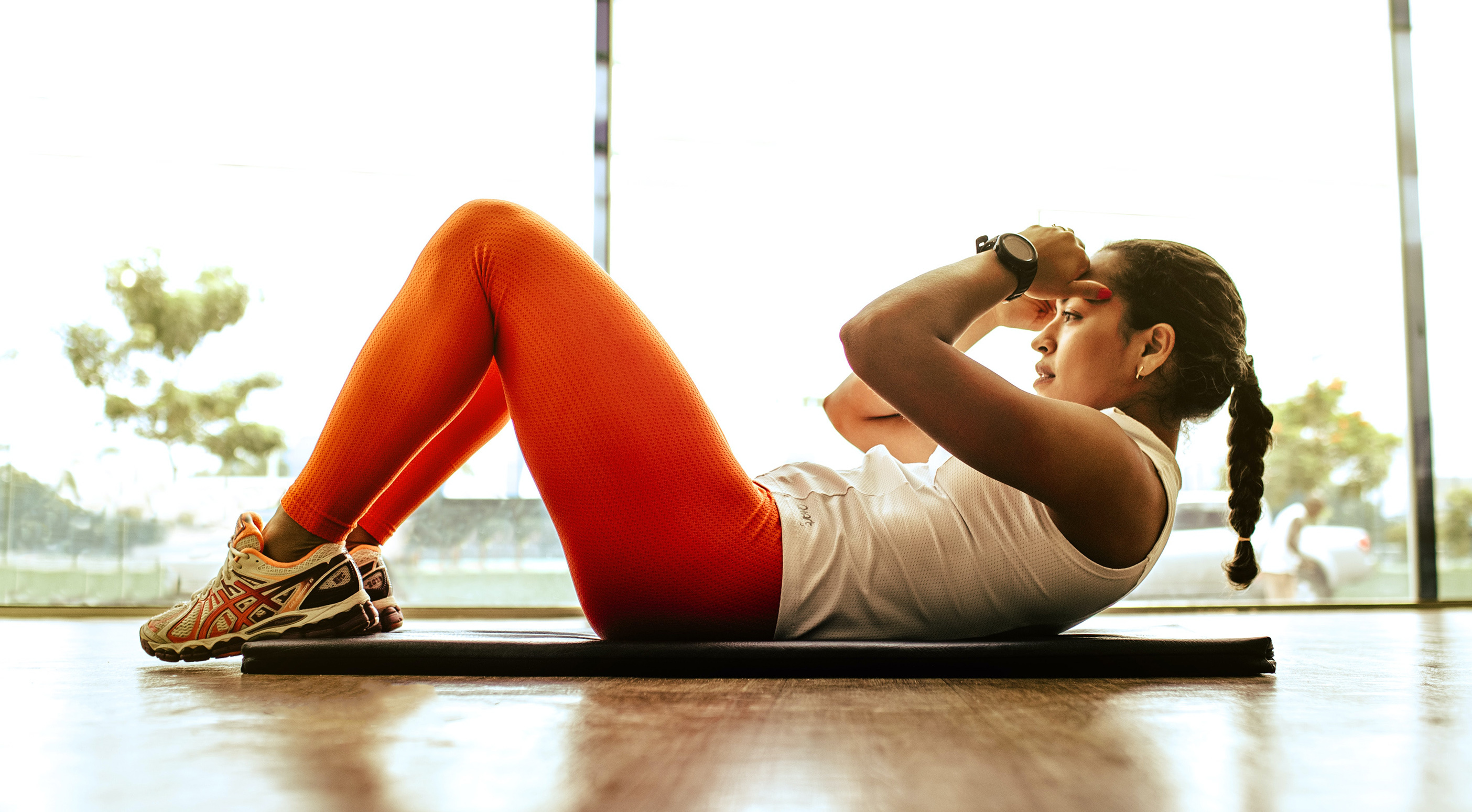 Young woman doing sit ups on a gym mat