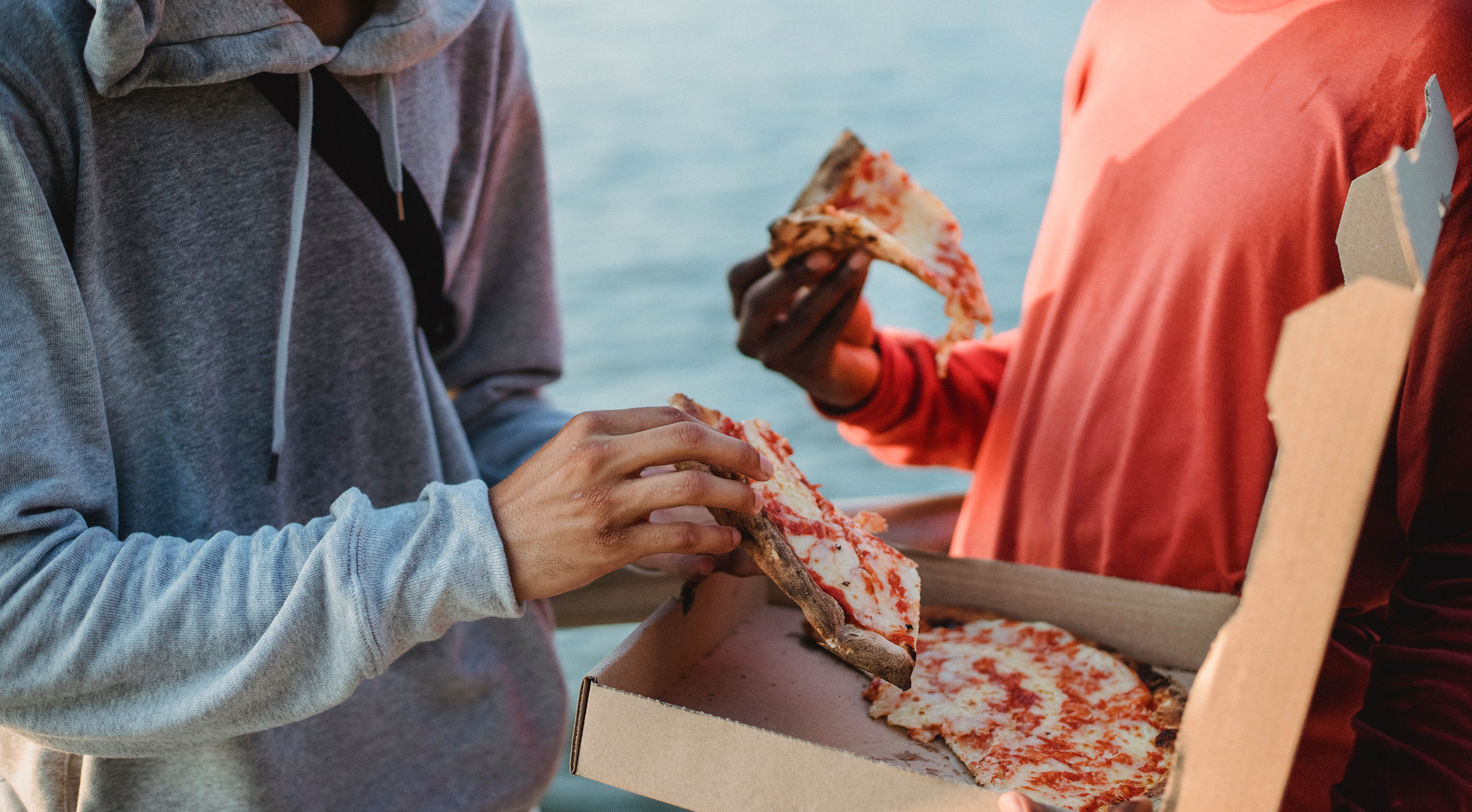 Two friends sharing a pizza outside
