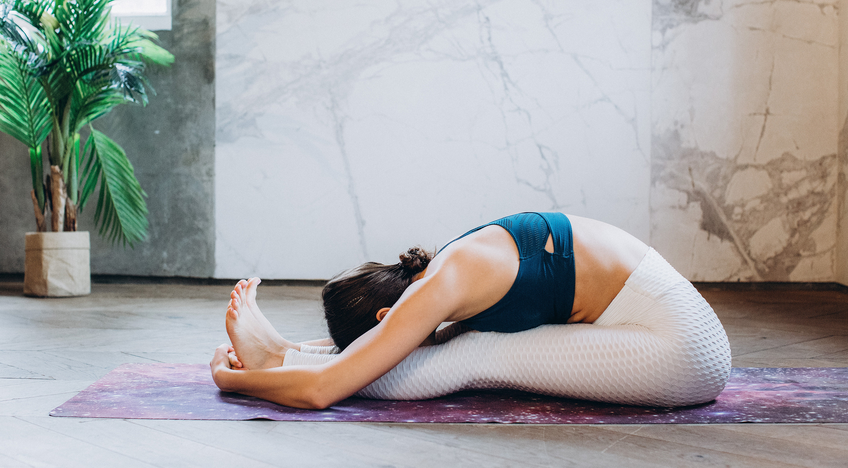 A woman sitting on the mat and touching to her right knee