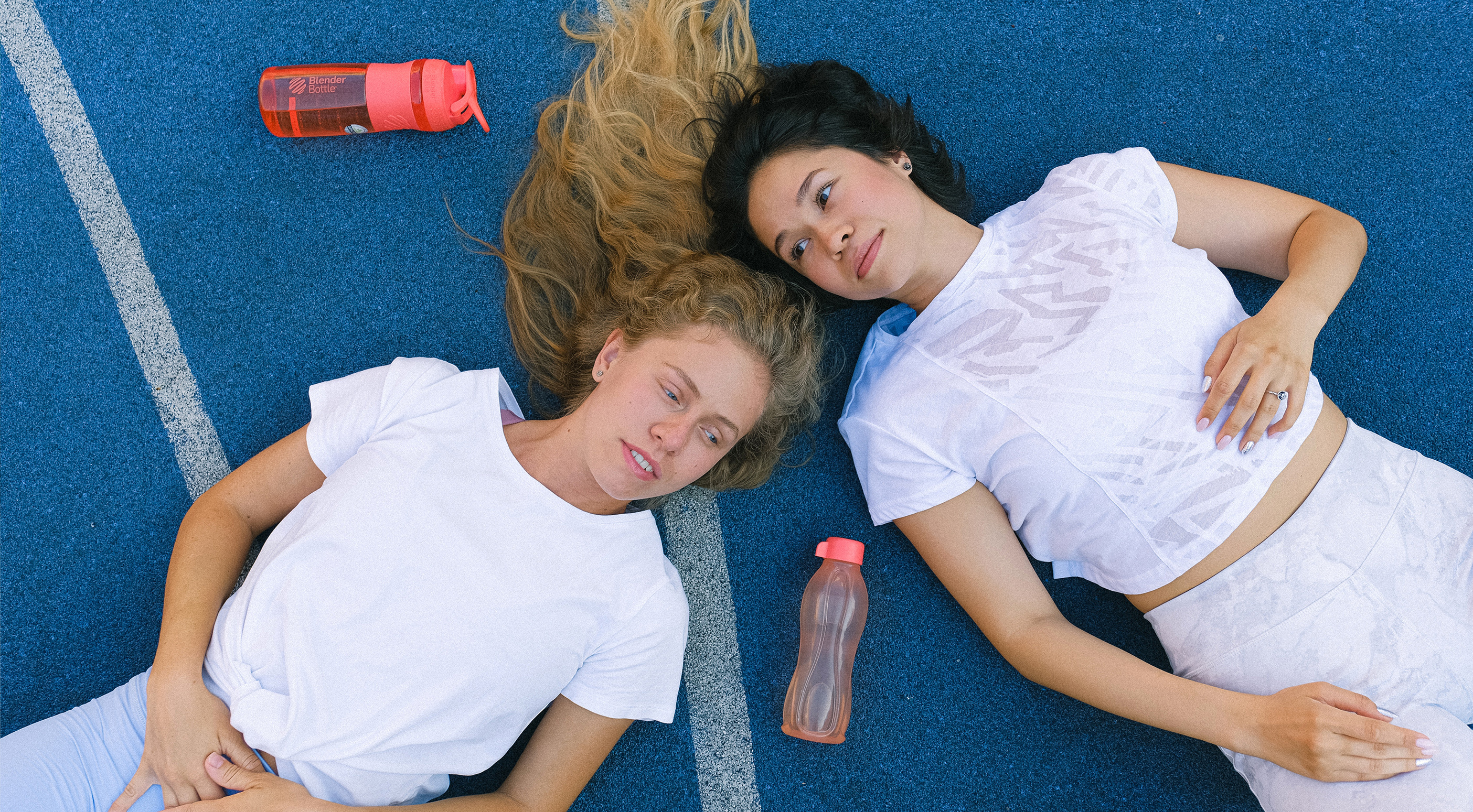 Two woman resting on the floor with gym clothes on
