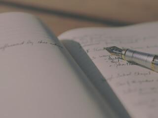 Ein Füllfederhalter liegt auf einer beschriebenen Seite eines zur beiden Seiten geöffneten Heftes