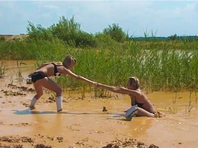Две волейболистки пытаются достать мяч из грязи