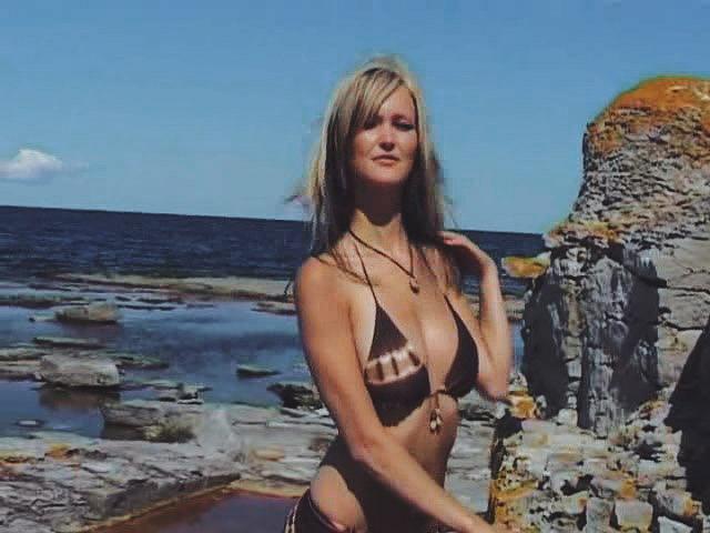 Модель в купальнике на каменистом берегу моря