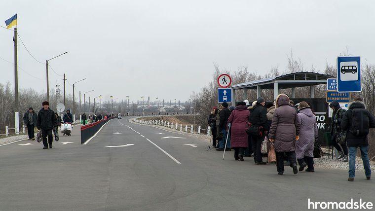 Люди чекають автобус на зупинці, їх тут тепер два. 80 відсотків тих, хто переходить міст — пенсіонери, Луганська область, 27 листопада 2019 року