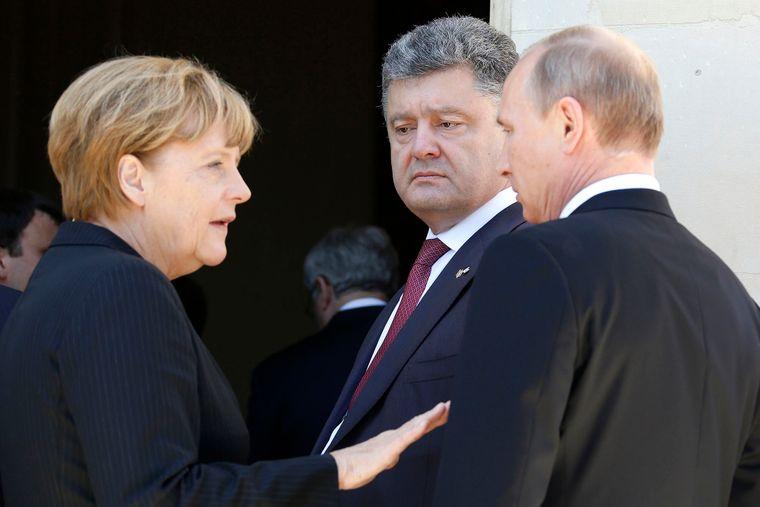 Зліва направо: канцлерка Німеччини Ангела Меркель, п'ятий президент України Петро Порошенко і президент Росії Володимир Путін у Бенувілі, Франція, 6 червня 2014 року