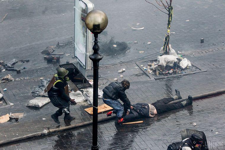 Протестувальники відтягують тяжко пораненого на вулиці Інститутській в Києві, 20 лютого 2014 року