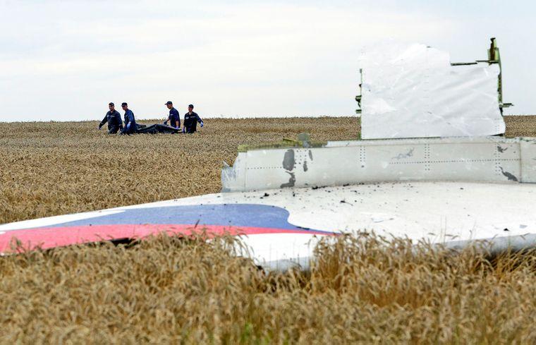 Рятувальники шукають і переносять тіла загиблих на місці катастрофи літака Boeing 777 Малазійських авіаліній рейсу MH17, який розбивлся на Донбасі, 19 липня 2014 року