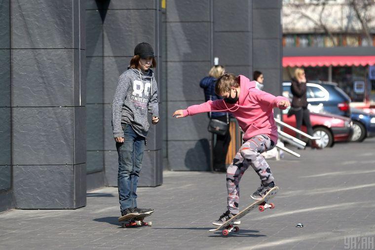 Діти в захисних масках катаються на скейті в Києві, 18 березня 2020 року. Усі заклади освіти в Україні вийшли з 12 березня на карантин через загрозу поширення коронавірусу