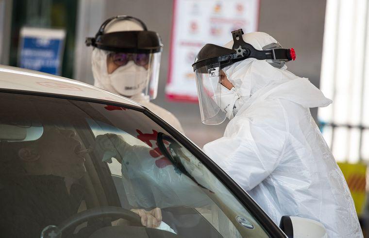 Медицинские работники берут образцы для выявления коронавируса у пациента в специальном центре тестирования прямо из окна автомобиля в городе Коян, Южная Корея, 6 марта 2020