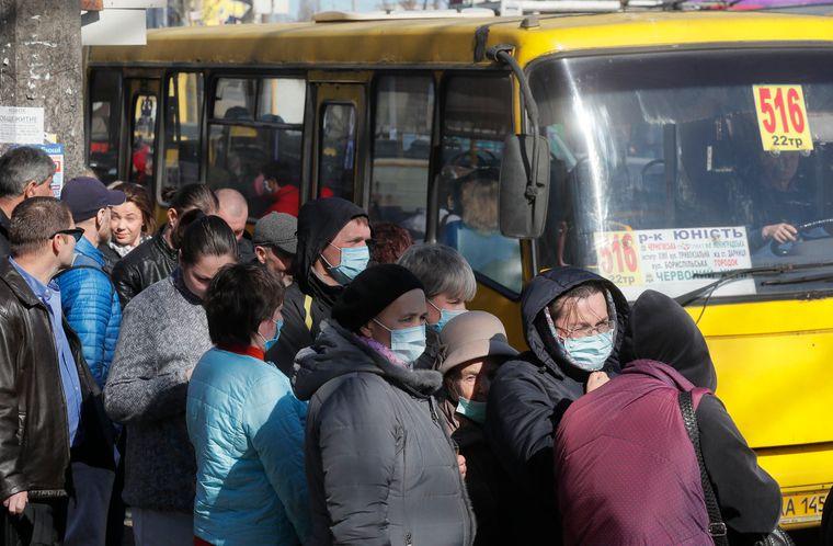 Пасажири чекають маршрутку на зупинці в Києві, 20 березня 2020 року