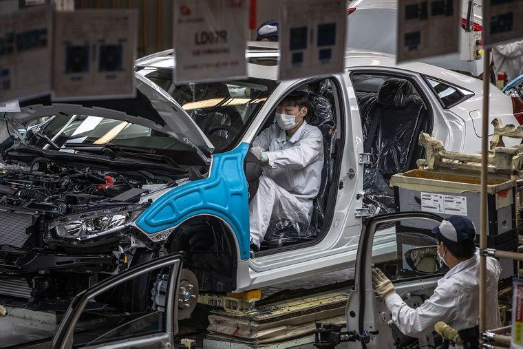 Працівники конвеєру на автозаводі Dongfeng Honda у місті Ухань, провинція Хубей, Китай, 8 квітня 2020 року. Китайський епіцентр коронавірусу на початку квітня почав відновлюватися після майже двомісячного суворого карантину