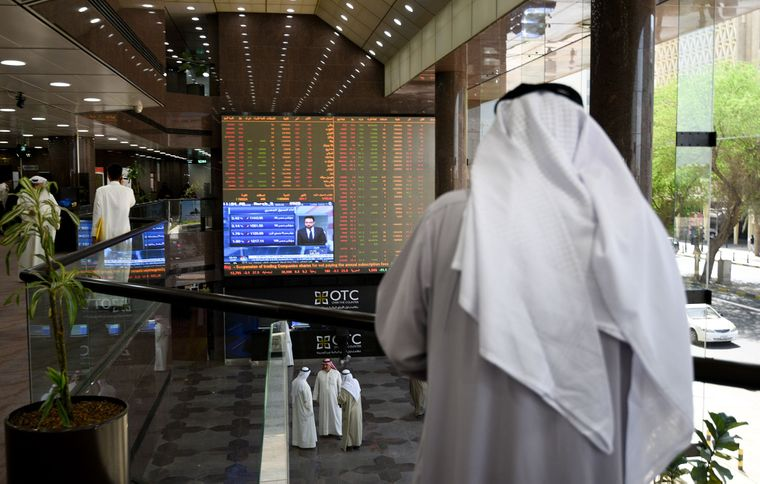 Торговцы ценными бумагами внутри зала Кувейтской фондовой биржи, Кувейт Сити, 9 марта 2020 года. Кризис, вызванный пандемией коронавируса, повлиял также на экономику стран Персидского залива, в частности — на нефтяную отрасль