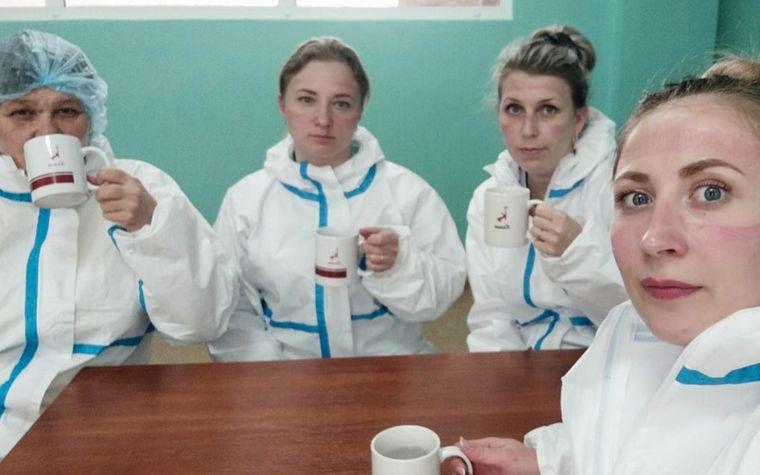 Медсестри зі слідами від масок та окуляр в перерві між роботою в інфекційному відділенні