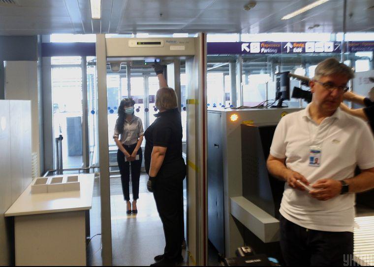 Міжнародний аеропорт «Бориспіль» готується до відкриття та відновлення пасажирських польотів, Київ, 13 червня 2020 року. Уявна пасажирка в захисній масці проходить перевірку металодетектором та процедуру вимірювання температури