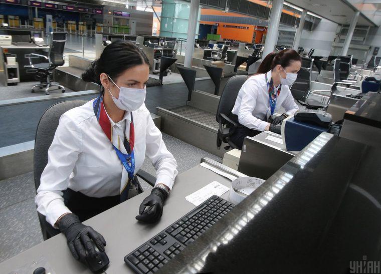 Міжнародний аеропорт «Бориспіль» готується до відкриття та відновлення пасажирських польотів, Київ, 13 червня 2020 року. Представниці авіакомпаній в захисних масках на стійках реєстрації польотів в аеропорту