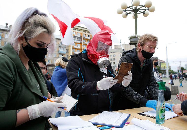 Активісти в захисних масках та рукавичках збирають підписи на підтримку опозиційних кандидатів на майбутніх президентських виборах у Мінську, Білорусь, 14 червня 2020 року