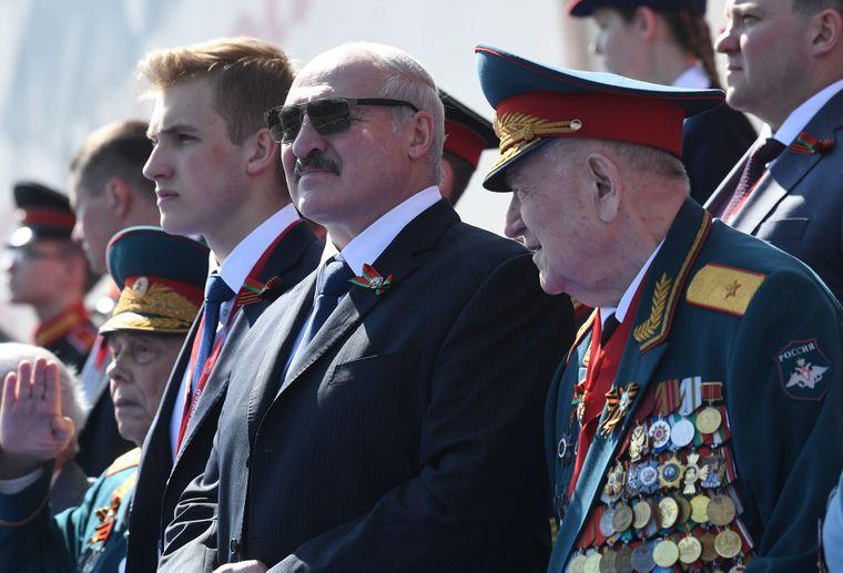 Президент Білорусі Олександр Лукашенко (в центрі) з сином Колею спостерігають за військовим парадом на Червоній площі в Москві, 24 червня 2020 року