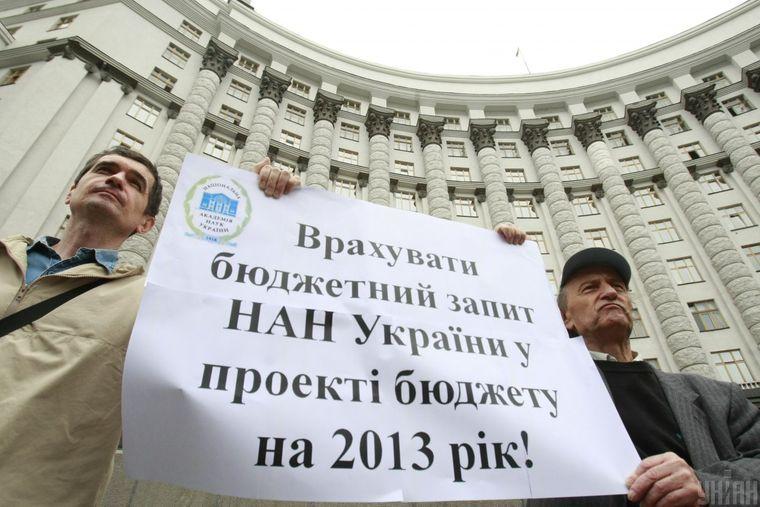 Ученый Национальной академии наук Украины держит плакат во время пикетирования здания Кабинета министров с требованием обеспечить достойную зарплату в научной сфере, 24 мая 2012 года.