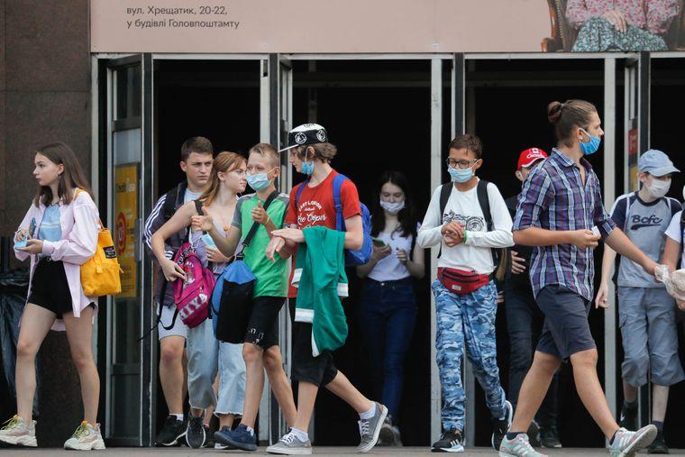 Украинцы в защитных масках выходят со станции метро во время длительной пандемии коронавируса COVID-19 в Киеве, Украина, 12 августа 2020 года.