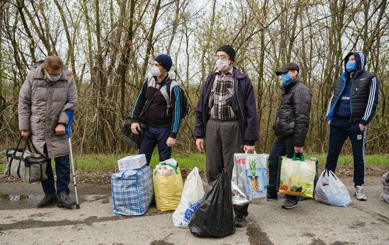 Обмененные пленные ждут со своими вещами во время обмена пленных между украинскими военными и пророссийскими боевиками, недалеко от пункта пропуска Майорское у оккупированного боевиками города Горловка, Донецкая область, Украина, 16 апреля 2020 года