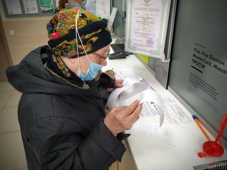 Пенсіонерка в медичній масці сплачує за житлово-комунальні послуги, в банку, під час карантину, в Києві.