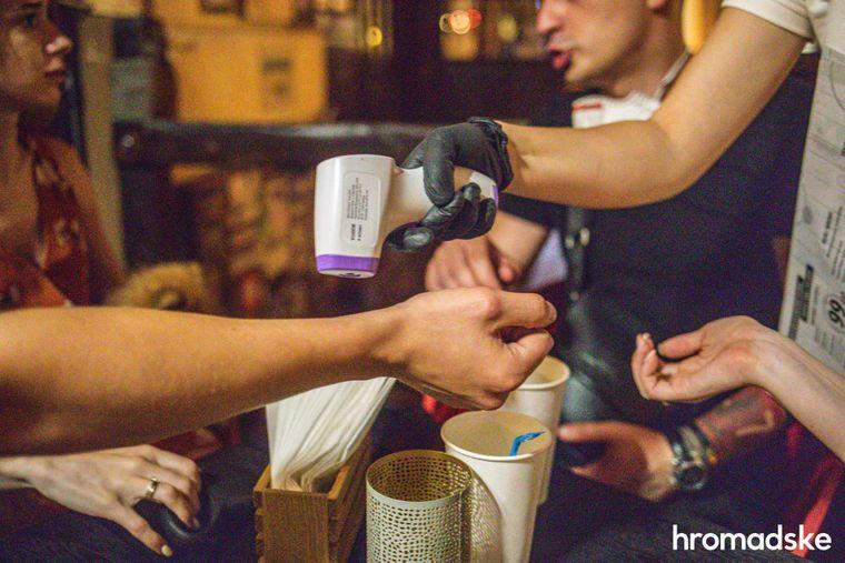Офіціантка кав'ярні міряє температуру перш ніж прийняти замовлення у Роксоляни та її друзів.