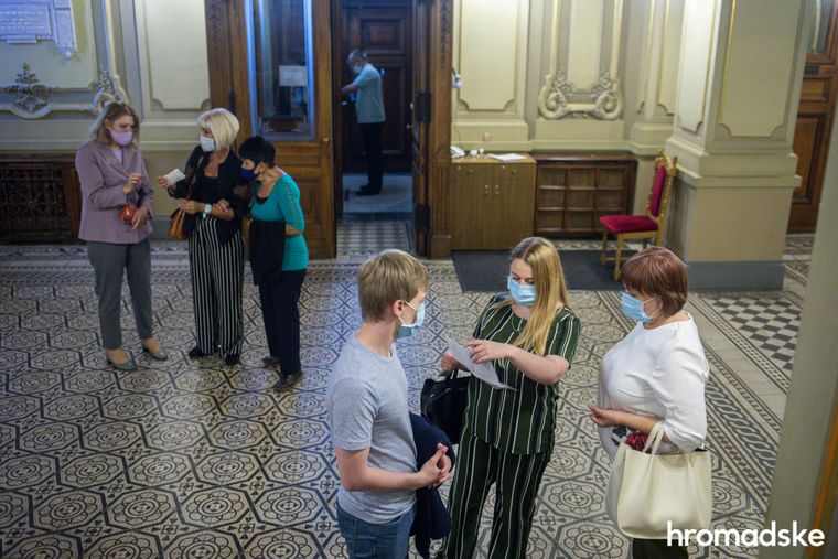 Глядачі в масках входять до Львівської національної опери перед початком вистави.