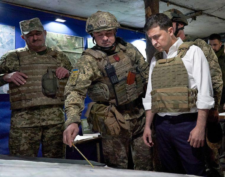 Президент України Володимир Зеленський слухає військовослужбовця під час поїздки до Донецької області на сході України.