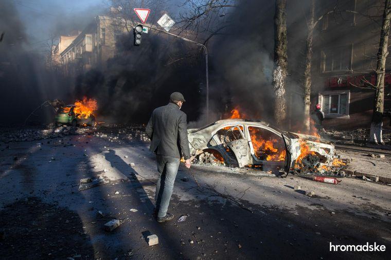Чоловік дивиться на автомобілі, спалені під час зіткнень між протестувальниками й силовиками на перетині вулиць Інститутської та Шовковичної в Києві, 18 лютого 2014 року