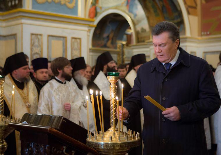 Колишній президент України Віктор Янукович ставить свічку, відвідуючи богослужіння з нагоди Дня Соборності та свободи в Успенському соборі в Києві, 22 січня 2014 року