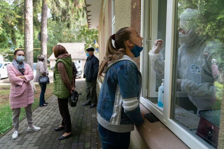 Медичний працівник збирає зразок для тесту на COVID-19 у жінки біля лікарні в селі Топорівці, Україна, 2 жовтня 2020 року.