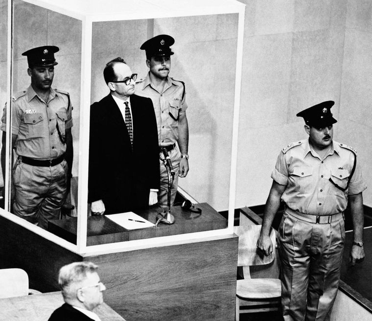 Адольфа Айхмана оточують охоронці, коли він стоїть у своїй скляній клітці для в'язнів, а судді Верховного суду Ізраїлю входять до зали суду, 29 травня 1962 року.