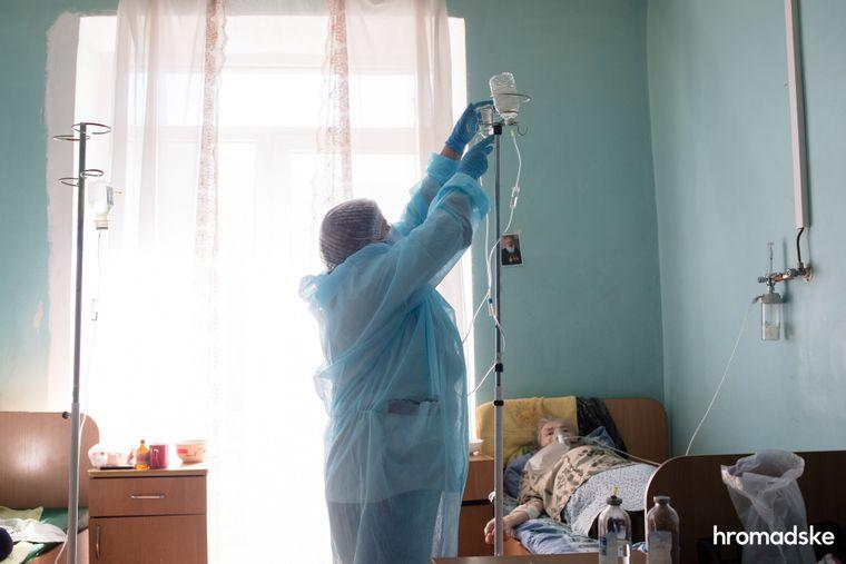 Медсестра встановлює крапельницю жінці з коронавірусом, яка лежить у палаті для інфекційних хворих у лікарні Яремча